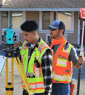 young workers learning surveying